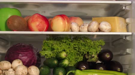 stocked : Fruits and vegetables on the shelves of the open refrigerator, closeup. Slow motion. Camera movement from left to right.