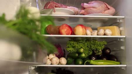 stocked : Open refrigerator with assortment of food and beverages. Fresh vegetables, fruit and meat on the refrigerator shelf. Close-up.