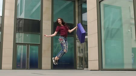 radość : Cute brunette jumping for joy in front of a commercial center after shopping. Slow motion.