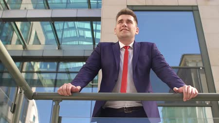 onto : Successful man in a blue suit stands leaning on the railing next to modern glass buildings resting outdoors.