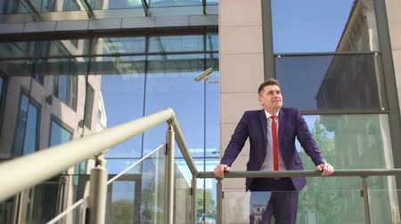 onto : Successful man in a blue suit stands leaning on the railing next to modern glass buildings resting outdoors. Wide shot. 4K