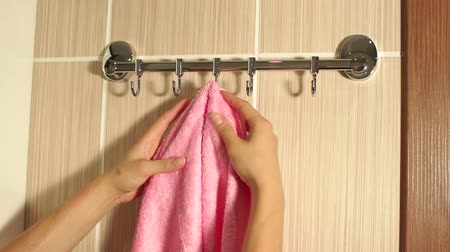 towel folded : Girl hangs a towel on the hook of the hanger. Girl hangs a towel on a hook in the bathroom, close-up.