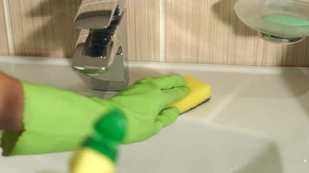 cleaning products : Close-up of female hands wearing protective gloves, cleaning bathroom sink with sponge. Girl washes the sink in bathroom with a washcloth. Slow motion.