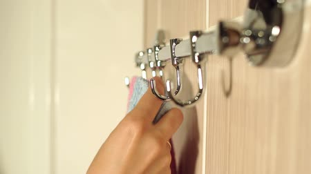 towel folded : Close-up of a towel rack in the bathroom. Girl hangs a blue towel on the hook of the hanger, close-up. Stock Footage