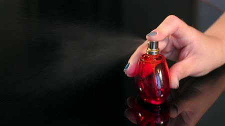 kolínská voda : Close-up of a girl Squirting perfume on a black background.