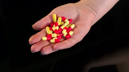 aspirina : Girl holding a handful of pills in hand on black background.
