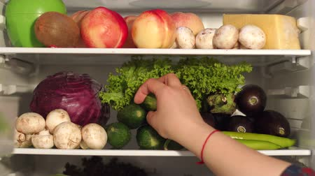 hűtőgép : Young woman takes out of the refrigerator cucumber. Woman taking food from the refrigerator. Close-up. 4K Stock mozgókép