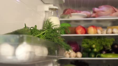 stocked : Open the fridge door with the milk, dill and products on the shelf. An open refrigerator door with food, close-up.