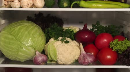 stocked : Vegetables on the shelves of the open refrigerator, close-up. Slow motion. Stock Footage