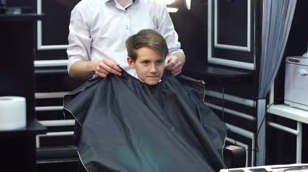 borbély : A male hairdresser puts on a young boy a protective cape before a haircut in the hairdresser. Stock mozgókép
