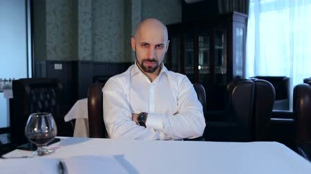 haughty : Portrait of a successful serious bald businessman in a restaurant at the table.