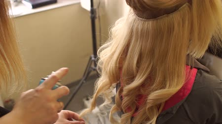 peruka : Close-up of hairdressers hands using hairspray on clients hair at salon. Hairdresser spray hair spray on the girls hair, close-up. Wideo