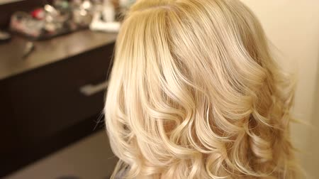 anelzinho : Hairdresser makes hairstyle girl with long blonde hair. Close-up. Hairdresser spray hair spray on the girls hair. Stock Footage