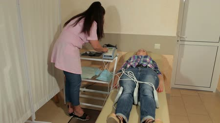 fizjoterapeuta : Magnetic therapy for young female patient in modern clinic, close-up. Magnet therapy system. Patient with doctor in medical office.