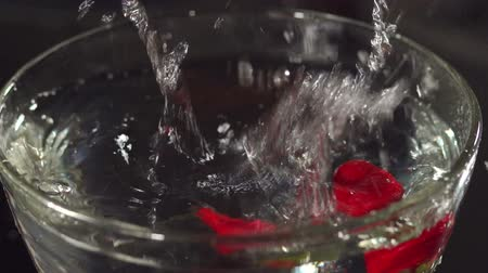 healthyfood : Close-up of a strawberry falling into a bowl with water, slow motion. Strawberry dropping into a bowl of water creating splashes. Stock Footage
