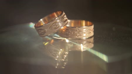 weddings : Close-up of two Golden wedding rings on a black glowing background.