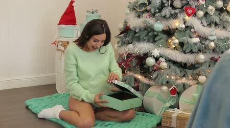 sock : A young pregnant girl in a warm sweater and socks sitting on the floor near the Christmas tree and opens the gift box. Pregnant girl near the Christmas tree with a gift. Stock Footage