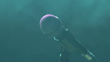mikrofon : Close-up of microphone on stage in the dark on a black smoky background. Slow motion. Wideo