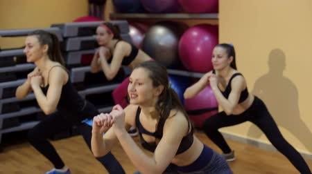 four legs : Four beautiful sports girls squats in the gym. Sport. Aerobics. Fitness. Healthy lifestyle. Stock Footage