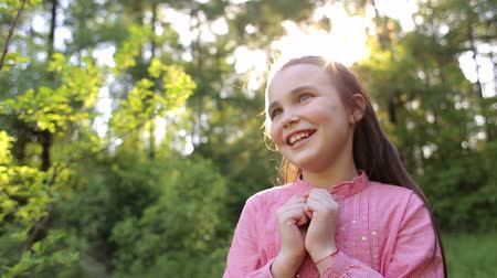 small park : Portrait of happy smiling little girl at sunset in the woods. Portrait of happy little girl 10 years in a Sunny Park on a background of green trees. Stock Footage