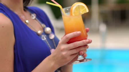 luxo : Close-up of young girl in swimsuit and jewelry holding a cocktail by the pool.