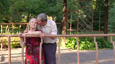 lasting : Grandpa kisses the old woman in the Park standing in a large gazebo. Caring grandpa kisses his old wife. Portrait of an elderly couple in gazebo in summer.