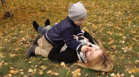 sarılmak : Happy mother and little child having fun lying on the ground in autumn Park. Happy family lying on the ground in the Park among the autumn leaves.