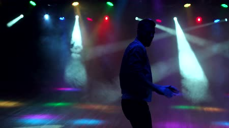 félrebeszél : Silhouette of a modern young man dancing on a dark stage in the light of multi-colored searchlights. Silhouette of dancer in the dark with smoke and concert lighting. Slow motion.