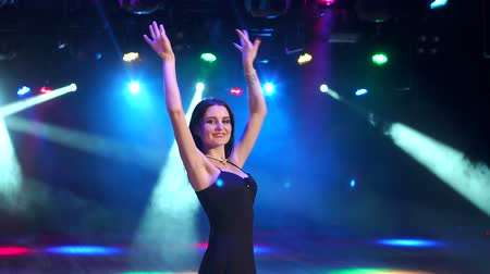 bachelorette party : Cute beautiful brunette in evening dress dancing at a bachelorette party on the background of bright spotlights.