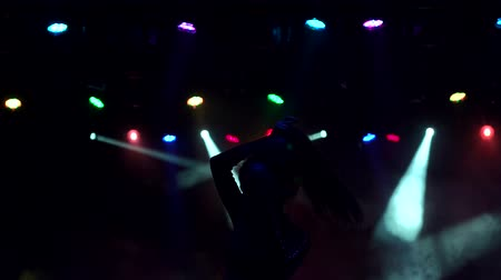 concert crowd : Silhouette of a slender dancing girl in a nightclub. Sexy girl dances in the dark with the light of multi-colored searchlights, slow movement.