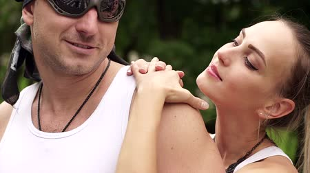 undershirt : Close-up of a couple of bikers in white shirts are standing arm in arm outdoors, girl kissing a guy in sunglasses and a bandana. Stock Footage