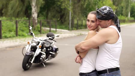 undershirt : Male biker in a white t-shirt and bandana hugging his girlfriend standing on an empty road in the background of a modern motorcycle. Stock Footage