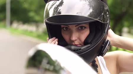 undershirt : Portrait of young sexy girl in the black helmet on a motorcycle. Portrait of a girl in a motorcycle helmet, close-up. Stock Footage