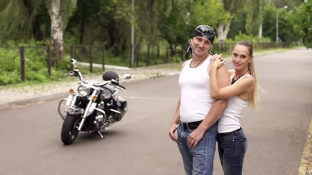 undershirt : Brutal couple of bikers standing in an embrace near the big motorcycle on the road. Stock Footage