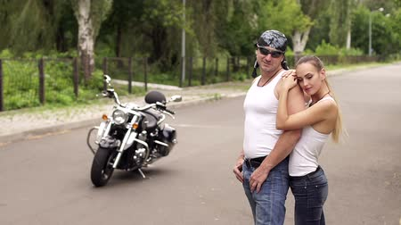 undershirt : Young couple of bikers wearing white undershirt hugging standing on the road near a modern motorcycle.