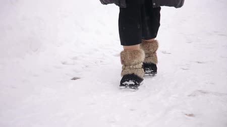 fur boots : A girl in fur warm winter boots walks through the snow in the park, close-up.