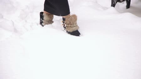 fur boots : Close-up of a girl in a black long dress and fur boots walks through deep snow in the park.