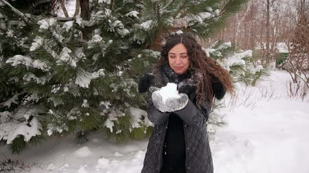 hófúvás : Cheerful pregnant girl blowing on snow in winter snow-covered park. Happy girl who is waiting for the child is walking and having fun in the winter park. Stock mozgókép