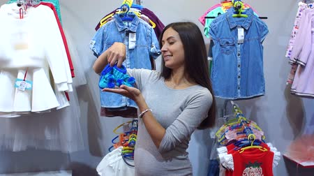 booties : Portrait of happy pregnant girl in a childrens clothing store, she holds in her hands the blue booties.
