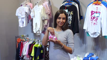 booties : Portrait of happy pregnant girl in a childrens clothing store, she holds in her hands the pink booties. Stock Footage