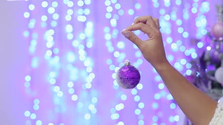 stříbřitý : The girl is holding a purple Christmas ball in her hands against the background of blurred flashing lights. Close-up. New Year. Christmas. Bokeh. Background. Dostupné videozáznamy