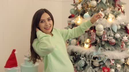 святки : Portrait of a beautiful pregnant girl with Christmas toy in the hands against the background of the Christmas tree.