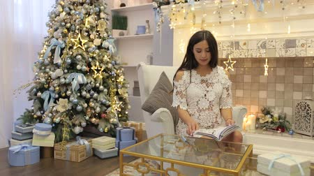 umutlu : Cute gentle pregnant woman sitting near beautiful decorated Christmas tree at home and reading book. Stok Video