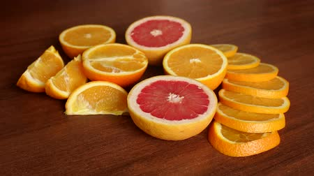 grejpfrut : Sliced citrus fruits, oranges and grapefruit, on wooden table, close-up. Abstract background with citrus-fruit of orange slices. Close-up. Sliced orange background.