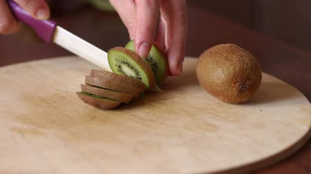 artigos de vidro : Close-up of womans hands slicing kiwi on wooden Board. Hand slicing a kiwi with a knife on wooden board, close-up.