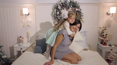 anne : The daughter hugs her pregnant mother tightly on the bed near the Christmas tree in the Christmas interior.