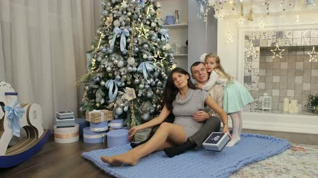 камин : Portrait of happy family on the background of the Christmas tree. Pregnant woman with her husband and daughter 4 years sit near Christmas tree with presents.