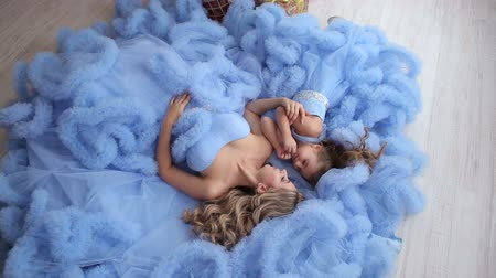 samoyed : Beautiful mother and her daughter dressed in the same blue fluffy dresses, they lie on the floor and posing for a photographer. Stock Footage