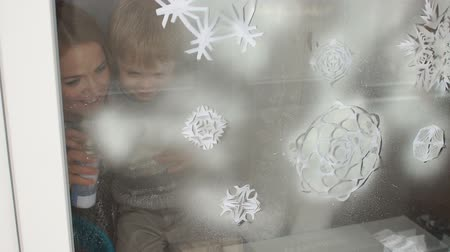 pulverização : Mom and her son decorate the windows for Christmas with snowflakes and artificial snow, they spray artificial snow on paper snowflakes on the window.