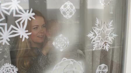 окропляет : Mom and her son decorate the windows for Christmas with snowflakes and artificial snow, they spray artificial snow on paper snowflakes on the window.
